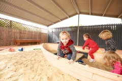boys and girls playing in a boat in the sand pit