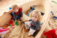 children playing in a boat in the sand pit