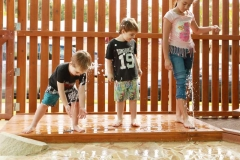 three children playing in mountain creeks water playground