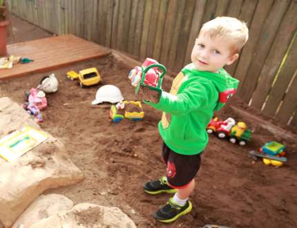 A boy playing in the dirt with a truck